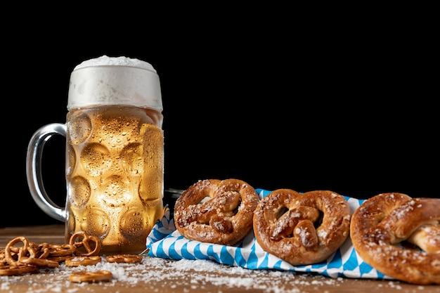 Jarra de cerveza con pretzels sobre una mesa Foto gratis