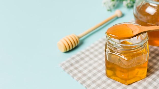 Jarra de miel con cuchara Foto gratis