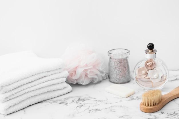 Jarra de sal de baño; toallas; esponja; cepillo; botella de jabón y perfume en superficie de mármol. Foto gratis