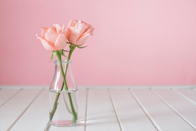 Jarrón de cristal bonito con dos flores Foto gratis