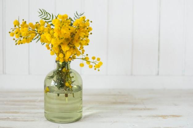 jarrn decorativo con flores bonitas sobre superficie de madera foto gratis