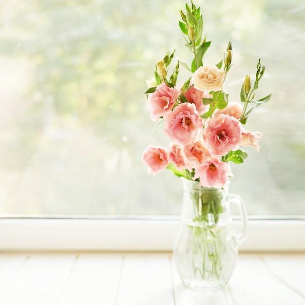 Jarrón con flores de eustoma sobre una mesa contra una ventana Foto Premium
