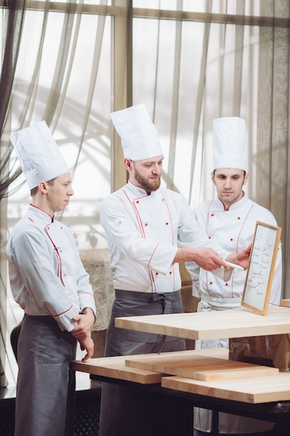 Jefe de cocina y su personal en la cocina interactuando con comerciales. Foto Premium