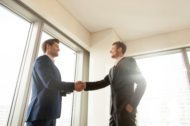 Jefe estrechando la mano y agradeciendo al trabajador por un buen trabajo Foto gratis