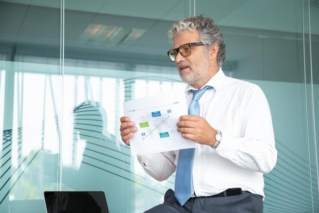 Jefe experimentado sentado y mostrando el plan estratégico Foto gratis