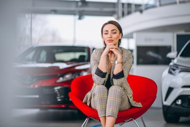 Jefe femenino en un showrrom de coche sentado en una silla roja Foto gratis
