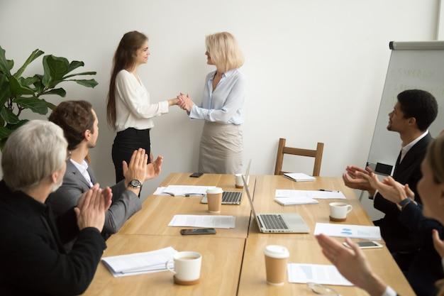 Jefe mayor de la empresaria que promueve agradecer a la empleada mientras que equipo aplaude Foto gratis