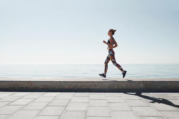 Jogging, mujer joven, funcionamiento, en tierra Foto gratis