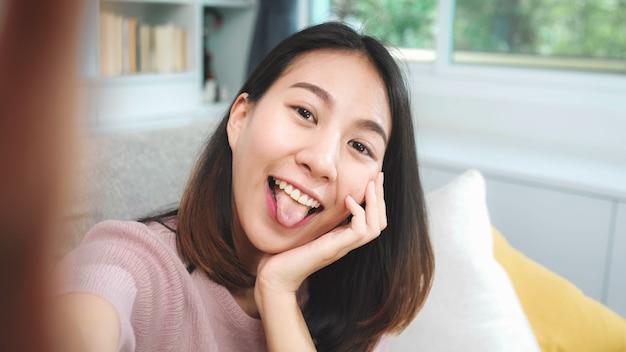 Joven adolescente asiática mujer vlog en casa, mujer usando teléfono inteligente haciendo video vlog a las redes sociales en la sala de estar. mujer de estilo de vida relajarse en concepto de mañana en casa. Foto gratis