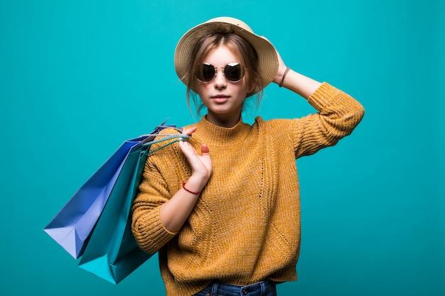Joven adolescente en gafas de sol y sombrero con bolsas de compras en sus manos sintiendo tan felicidad aislado en la pared verde Foto gratis