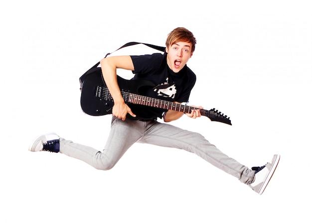 Joven adolescente saltando con guitarra Foto gratis
