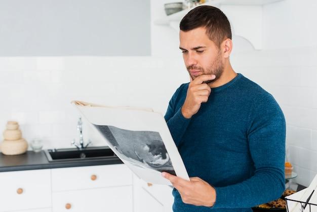 Joven adulto está leyendo el periódico en la cocina Foto gratis