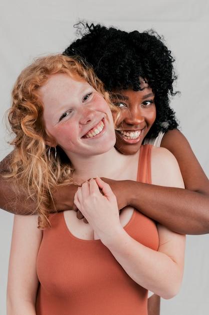 Una joven africana abrazando a su amiga caucásica por detrás Foto gratis