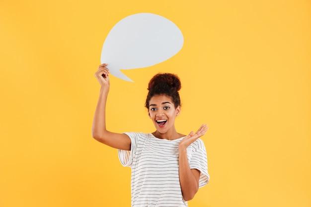 Joven africana pensativa feliz dama y sosteniendo el bocadillo en blanco aislado sobre amarillo Foto gratis