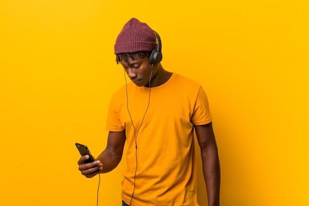 Joven africana de pie sobre un fondo amarillo con un sombrero escuchando música con un teléfono Foto Premium