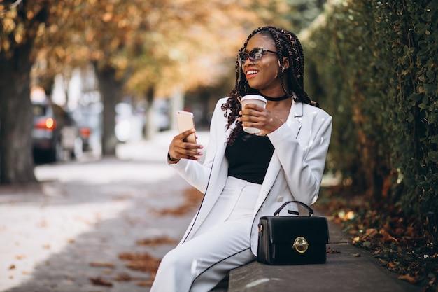 Joven africana tomando café y usando el teléfono Foto gratis