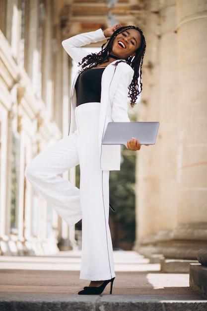 Joven Africana Vestida De Blanco Usando Laptop Foto Gratis