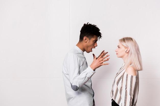 Un joven africano gritando a su novia contra la pared blanca Foto gratis
