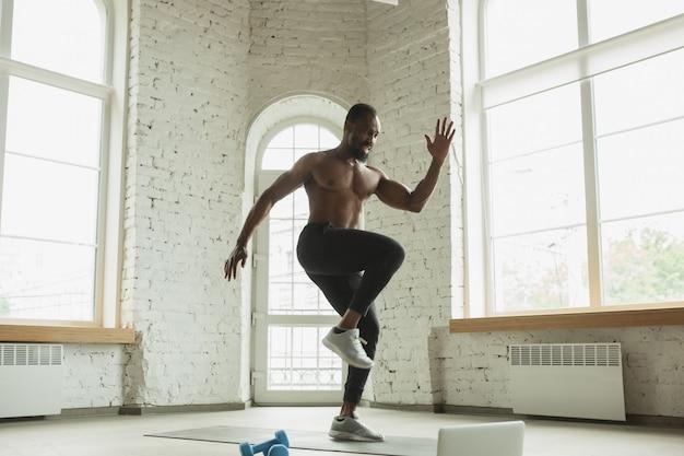 Joven afroamericano entrenando en casa, haciendo ejercicios de fitness, aeróbico. Foto gratis