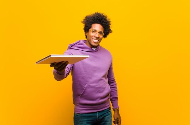 Joven afroamericano con un libro sobre fondo naranja Foto Premium