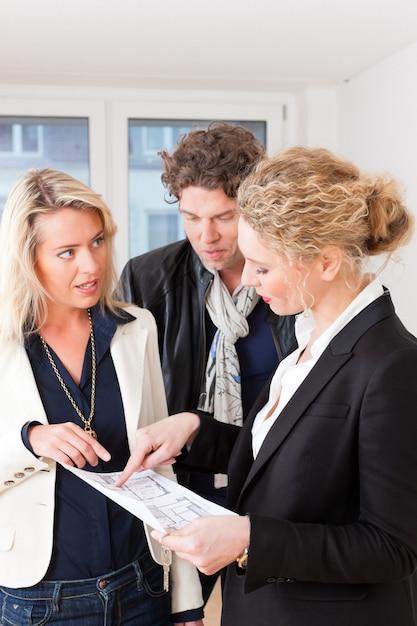 Joven agente de bienes raíces explica contrato de arrendamiento para pareja Foto Premium