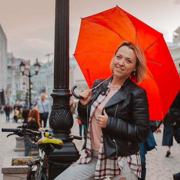Joven alegre bajo un paraguas rojo en el centro de la ciudad en otoño Foto Premium