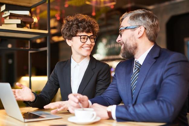 Joven analista o corredor exitoso que muestra los datos en línea de su colega mientras discute los cambios en la tasa financiera Foto Premium