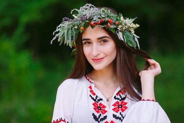 Una joven de apariencia eslava con una corona de flores silvestres en el verano. Foto Premium