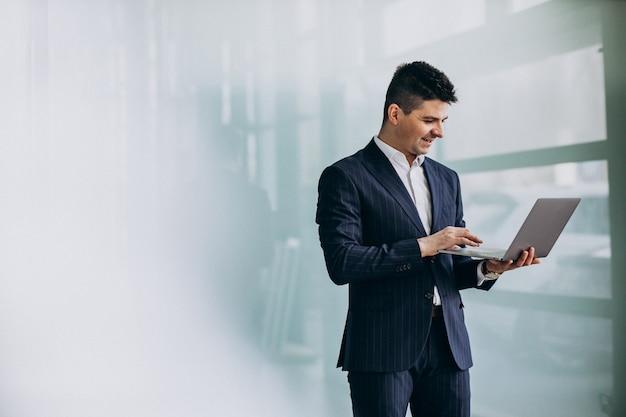 Joven apuesto hombre de negocios con ordenador portátil en la oficina Foto gratis