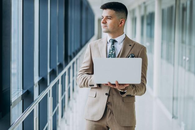 Joven apuesto hombre de negocios de pie con el portátil en la oficina Foto gratis