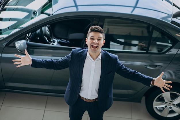 Joven apuesto hombre de negocios en un showrrom de coches Foto gratis