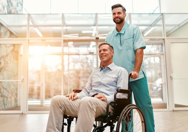 Un joven apuesto médico con su anciano discapacitado en silla de ruedas recorre los pasillos de una clínica moderna. Foto Premium