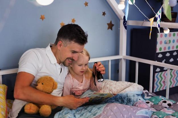 Joven apuesto padre y su hija leyendo un libro con una linterna mientras está sentado debajo de la cubierta en la cama Foto Premium
