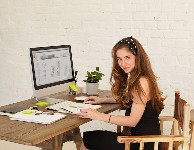 Joven arquitecto mirando y sonriendo mientras trabajaba en la oficina. atractiva mujer joven estudiando planes nuevo edificio de oficinas sentado en el escritorio en la oficina Foto gratis