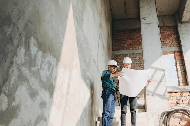 Joven arquitecto mostrándole a su propietario cómo avanzan las obras del edificio. Foto Premium