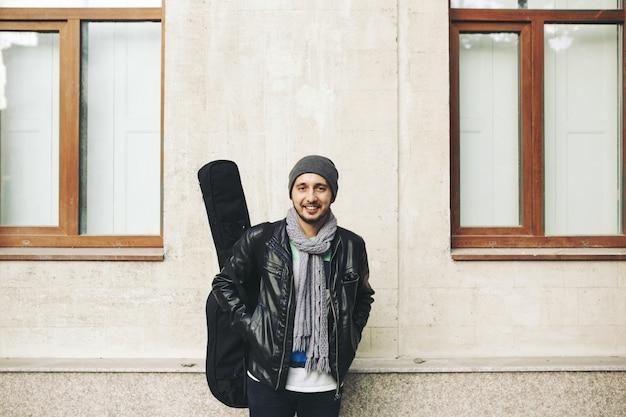 Joven artista callejero atractivo con su guitarra Foto gratis