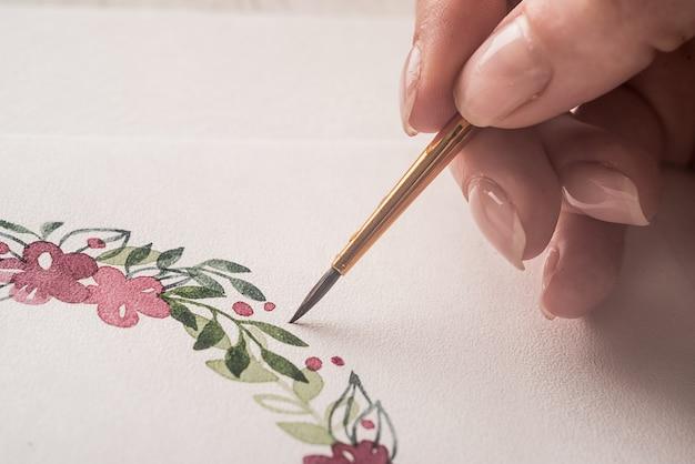 Joven artista dibujo patrón de flores con pintura de acuarela y pincel sobre papel en el lugar de trabajo Foto gratis