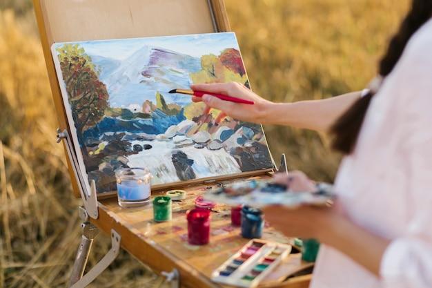 Joven artista pintando a mano en la naturaleza Foto gratis