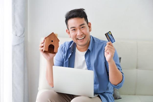 Joven asiática en camisa azul con computadora portátil y tarjeta de crédito y modelo de casa pequeña mostrando para préstamo bancario por concepto de casa en la sala de estar Foto Premium