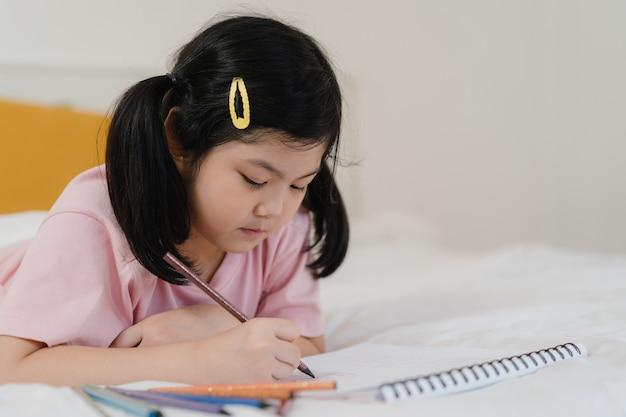 Joven asiática dibujo en casa. asia japonés mujer niño niño relajarse descansar diversión feliz dibujar dibujos animados en cuaderno de dibujo antes de dormir acostado en la cama, sentir comodidad y calma en el dormitorio en concepto de noche. Foto gratis