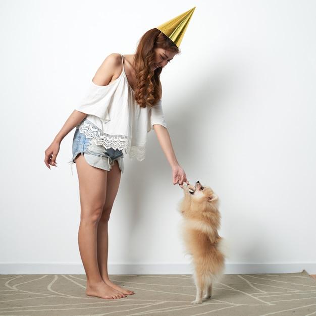 Joven asiática en divertido sombrero de fiesta jugando en casa con un pequeño perro mascota Foto gratis