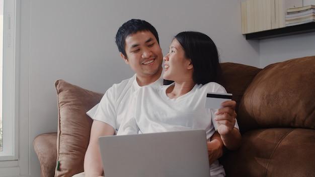Joven asiática embarazada pareja de compras en línea en casa. mamá y papá se sienten felices usando la tecnología portátil y la tarjeta de crédito comprando productos para bebés mientras están acostados en el sofá de la sala de estar en casa. Foto gratis