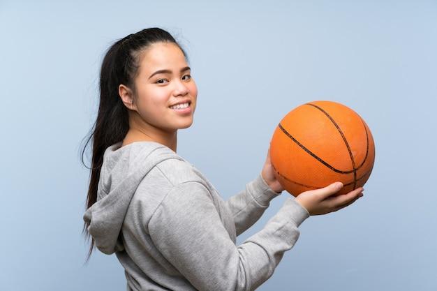 Joven asiática jugando baloncesto sobre pared aislada Foto Premium