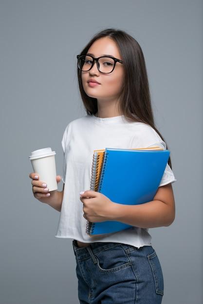 Joven asiática con portátil y café para ir en manos de pie aislado sobre fondo gris Foto gratis