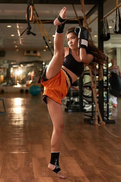 Joven asiática practicando boxeo muay thai en un gimnasio Foto gratis