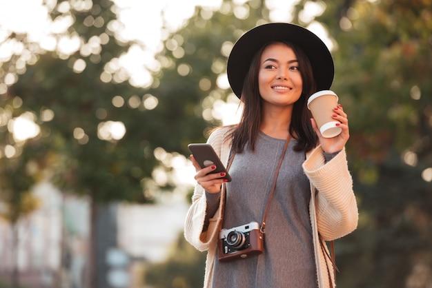 Joven asiática en sombrero negro tomando café y sosteniendo el teléfono móvil mientras camina en el parque al aire libre Foto gratis