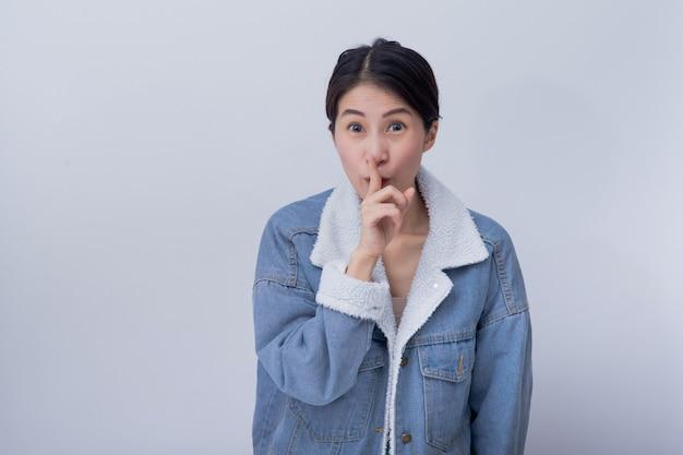 Joven asiática sonriente excitada mujer mostrando su mano con expresión sintiéndose sorprendida y asombrada, positiva chica caucásica vistiendo ropa casual azul Foto Premium