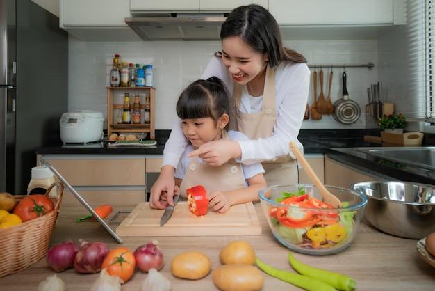Joven asiática y su hija cocinar ensalada para el almuerzo. Foto Premium