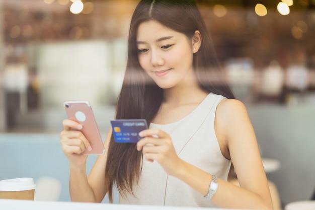 Joven asiática con tarjeta de crédito con teléfono móvil para compras en línea en la cafetería o espacio de coworking junto al espejo de la ventana, billetera de dinero de tecnología y concepto de pago en línea, maqueta de tarjeta de crédito Foto Premium