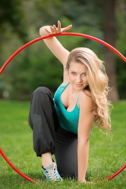 Joven atleta con hula-hoop en el parque Foto gratis
